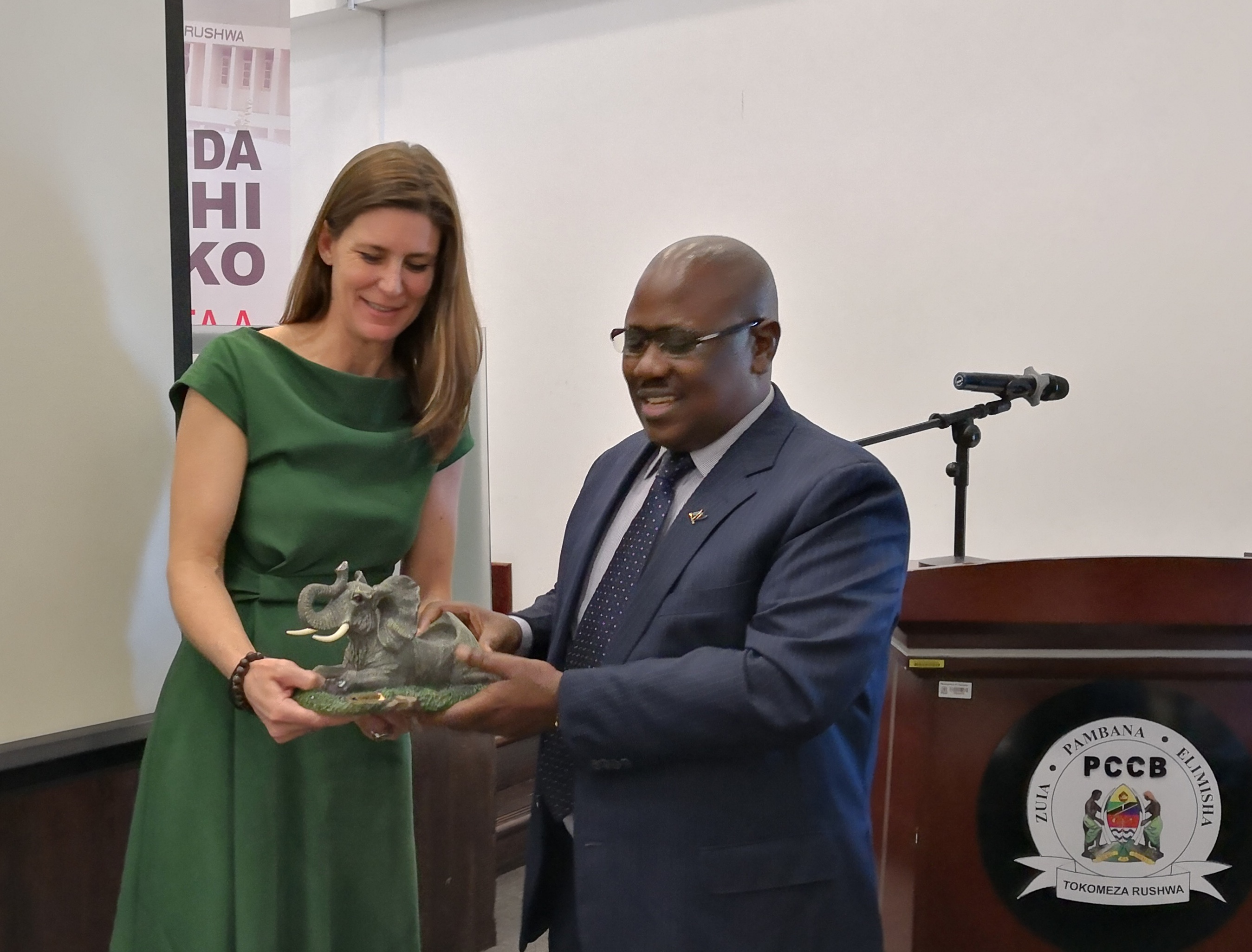 Gretta Fenner receives elephant sculpture from the Tanzanian PCCB