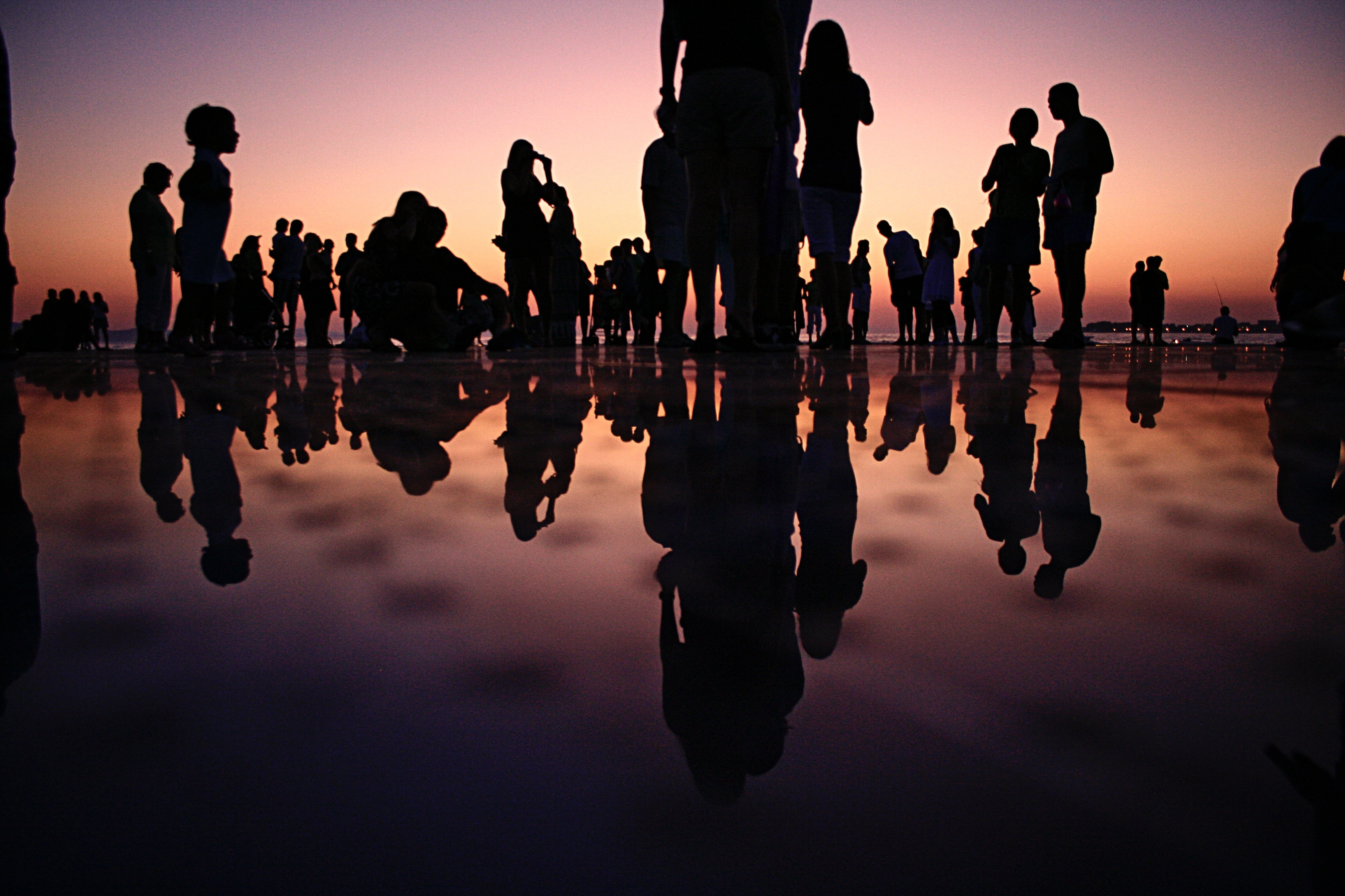 Silhouetted people standing on a mirrored surface