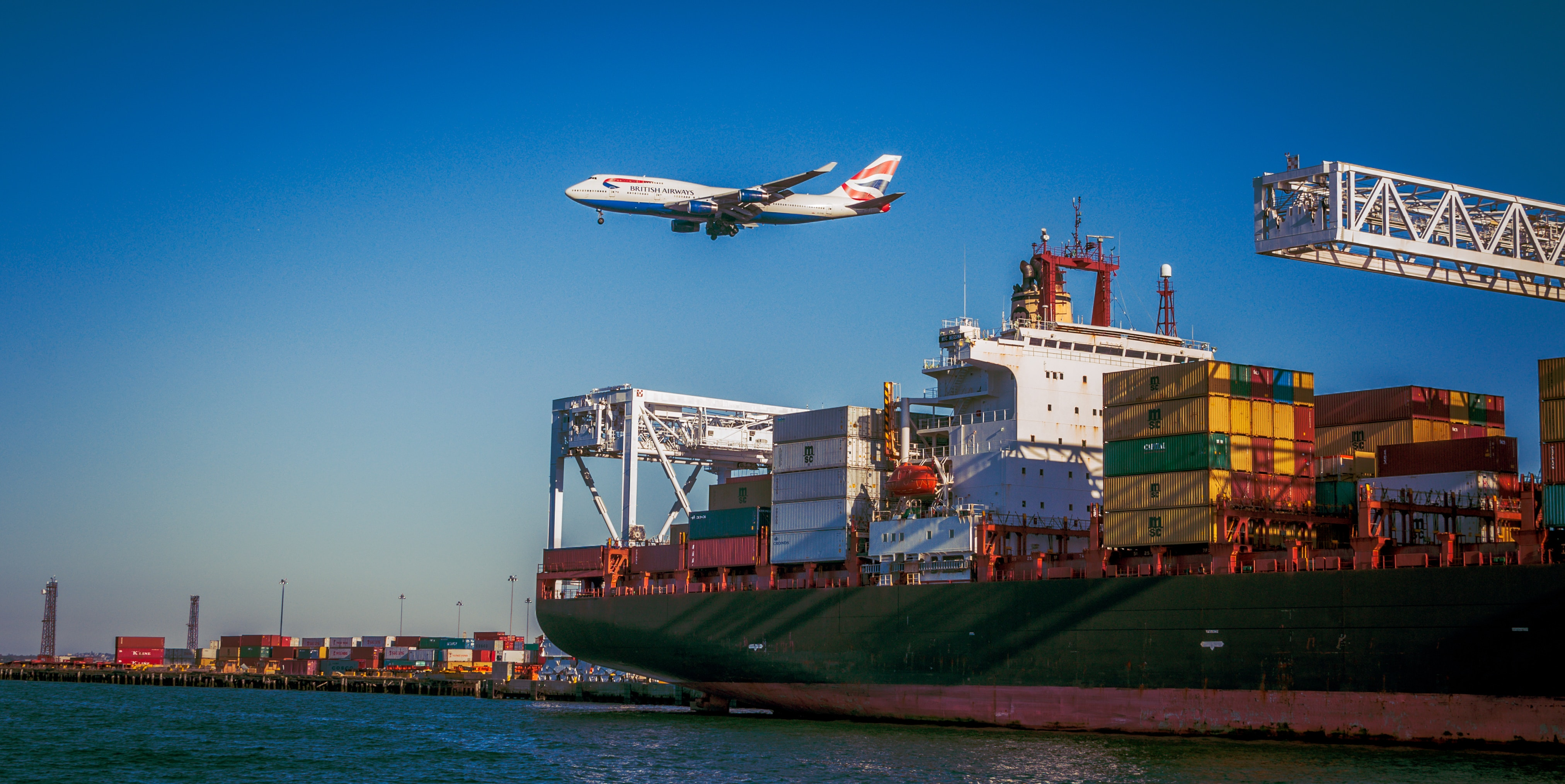Aeroplane over container shop. Photo by VanveenJF on Unsplash.