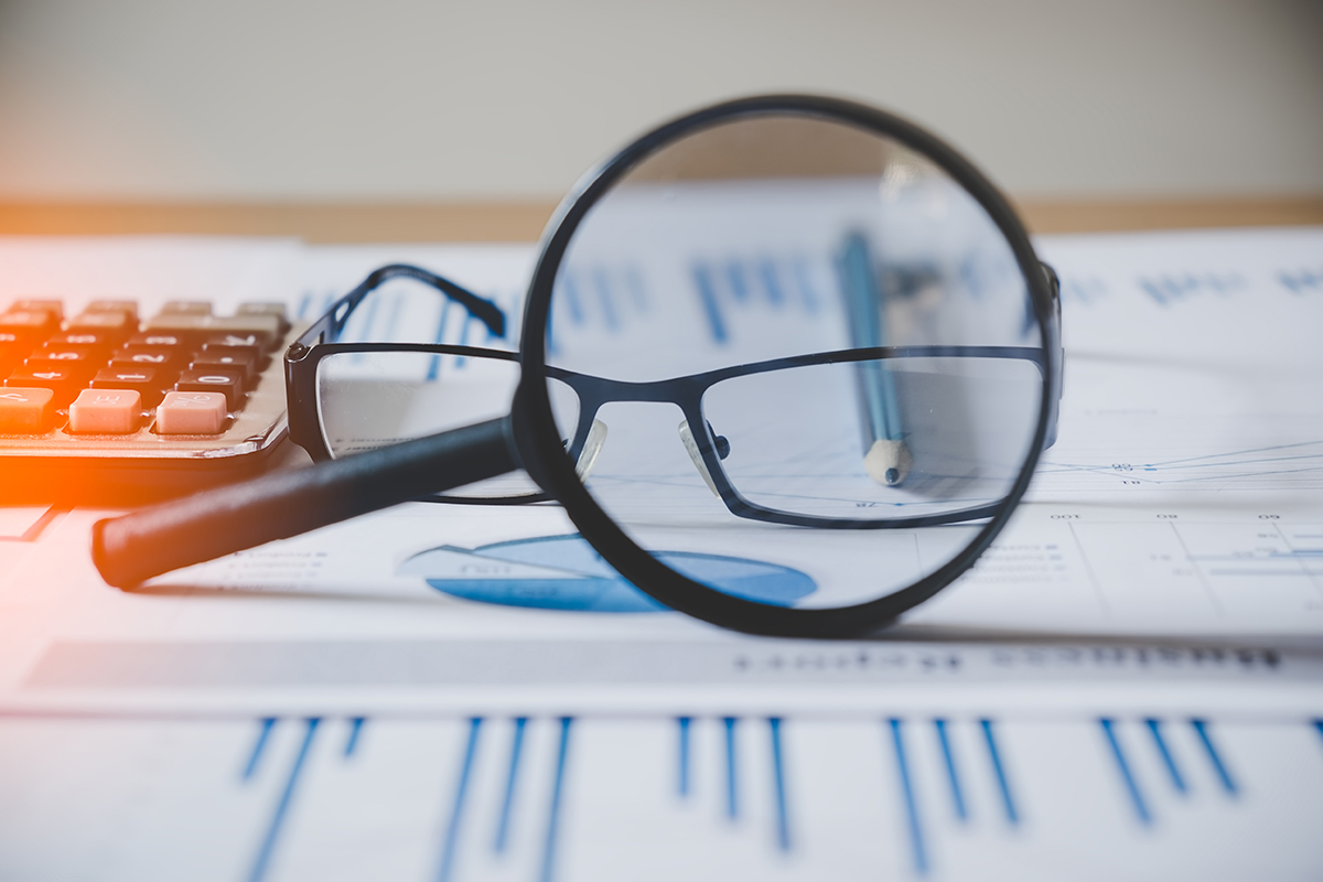 Magnifying glass and glasses on financial information