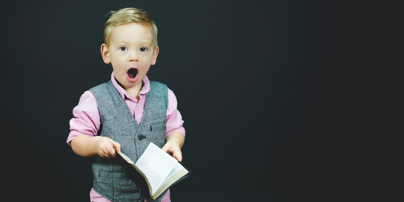 Small boy holding a book looking surprised. Photo by Ben White on Unsplash