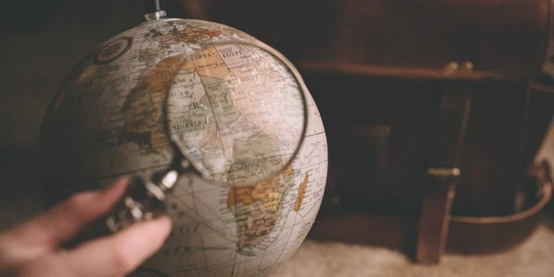Magnifying glass above a globe. Photo by Clay Banks on Unsplash.