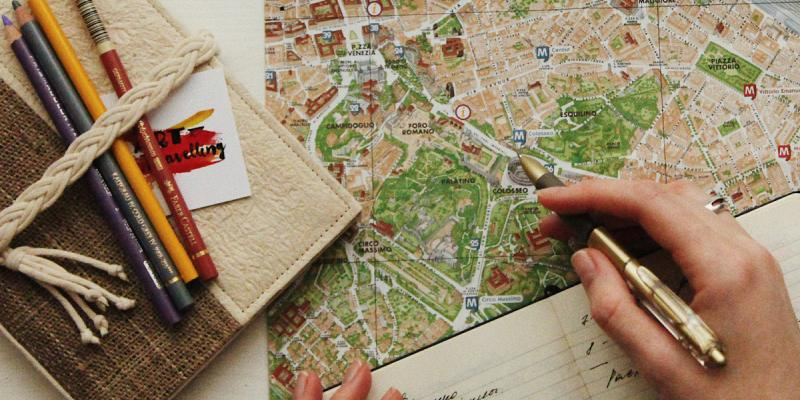 Map, book, pencils. Photo by oxana v on Unsplash